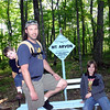 "Scott, James and Steven posing by the ""highest point in Michigan"" sign"